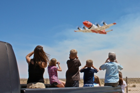 A family watches firefighters take off from Fox Field to fight the Crown fire.